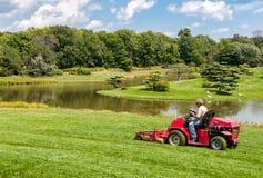 有拖拉机刈草机的工作者在芝加哥植物园里 免版税库存图片