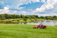 有拖拉机刈草机的工作者在芝加哥植物园里 免版税库存照片