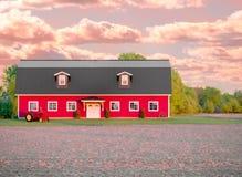 有拖拉机和日落的红色谷仓 免版税库存照片
