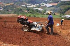 有拖拉机的农夫在领域 免版税库存图片