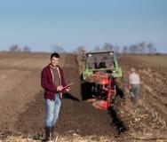 有拖拉机的农夫在领域 免版税库存照片