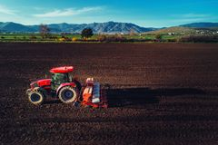 有拖拉机种子庄稼的农夫在领域 图库摄影