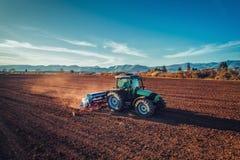 有拖拉机种子庄稼的农夫在领域 库存图片