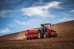 有拖拉机种子庄稼的农夫在领域 免版税库存照片