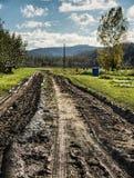 有拖拉机车轮痕迹的泥泞的农场马路 库存图片