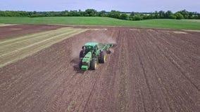有拖车的农用拖拉机耕的工作的在可耕的领域 种田天线 股票视频