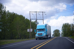 有拖车的半蓝色卡车在绿色树高速公路 免版税库存图片