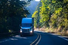 有拖车的现代半蓝色卡车在绿色弯曲道路 库存照片