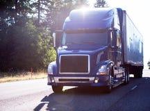 有拖车的现代黑暗的大半船具蓝色卡车在路 库存照片