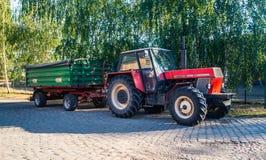 有拖车的老农用拖拉机 库存图片