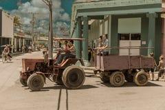 有拖车运载的人民的拖拉机在街道上 免版税库存图片