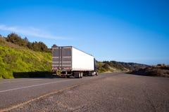 有拖车驱动的半黑色卡车在有绿色的直路 免版税库存照片