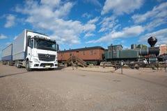 有拖车`奔驰车Actros `的现代欧洲卡车在一列老火车在一晴朗的6月天 城市芬兰kotka横向公园岩石sapokka视图 免版税库存图片