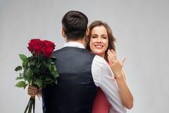 有拥抱人的定婚戒指和玫瑰的妇女 免版税库存图片