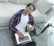 有拥抱他的狗和坐在长沙发附近的膝上型计算机的英俊的人 图库摄影