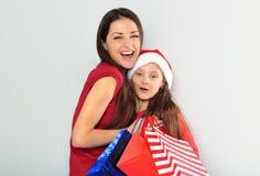 有拥抱充满爱她逗人喜爱的joying的女儿和拿着圣诞礼物的开放嘴的愉快的笑的母亲在圣诞老人帽子 库存图片