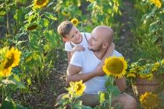 有拥抱在向日葵的领域的儿子的爸爸 儿子容忍他的向日葵的领域的父亲 免版税库存图片