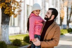 有拥抱在秋天成套装备的女儿的愉快的父亲 库存图片