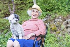 有拥抱她的在山的草帽的美丽的资深微笑的妇女狗 库存照片