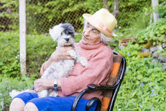 有拥抱她的在山的草帽的美丽的资深微笑的妇女狗 免版税库存图片