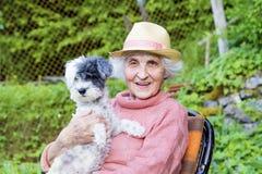 有拥抱她的在山的草帽的美丽的资深微笑的妇女狗 库存图片