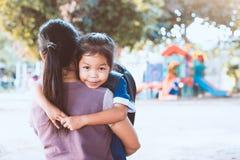 有拥抱她的母亲的背包的逗人喜爱的亚裔学生女孩 免版税图库摄影