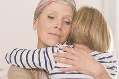 有拥抱孩子的肿瘤的母亲 库存图片