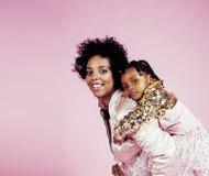 有拥抱小逗人喜爱的女儿的,愉快微笑年轻俏丽的非裔美国人的母亲在桃红色背景,生活方式 免版税库存照片