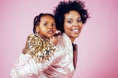 有拥抱小逗人喜爱的女儿的,愉快微笑年轻俏丽的非裔美国人的母亲在桃红色背景,生活方式 图库摄影