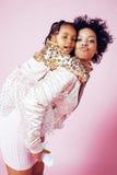 有拥抱小逗人喜爱的女儿的,愉快微笑年轻俏丽的非裔美国人的母亲在桃红色背景,生活方式 库存照片