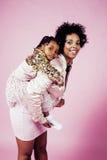 有拥抱小逗人喜爱的女儿的,愉快微笑年轻俏丽的非裔美国人的母亲在桃红色背景,生活方式 库存图片
