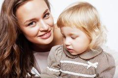 有拥抱小逗人喜爱的女儿的年轻人相当时髦的母亲,愉快的微笑的家庭,生活方式人概念 图库摄影