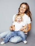 有拥抱小逗人喜爱的白肤金发的女儿的年轻人相当时髦的母亲,愉快的微笑的家庭,生活方式人概念 图库摄影
