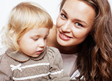 有拥抱小逗人喜爱的白肤金发的女儿的年轻人相当时髦的母亲,愉快的微笑的真正的家庭,生活方式人概念 免版税库存图片