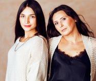 有拥抱成熟的母亲的,时尚st逗人喜爱的相当青少年的女儿 图库摄影