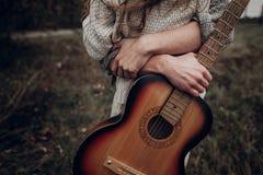 有拥抱他的有风领域的吉他的人boho吉普赛妇女 Atm 库存照片