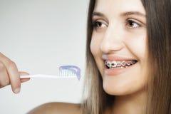 有括号和牙刷的愉快的女孩 免版税库存图片