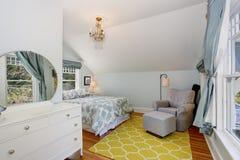 有拱顶式顶棚和硬木地板的小蓝色和黄色在楼上卧室 免版税库存照片