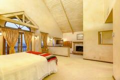 有拱顶式顶棚和a的明亮,开放和温暖的主卧室 库存图片