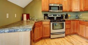 有拱顶式顶棚的厨房室在轻的橄榄色的口气 库存照片