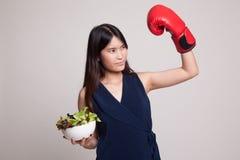 有拳击手套和沙拉的年轻亚裔妇女 免版税库存图片