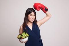 有拳击手套和沙拉的年轻亚裔妇女 库存照片