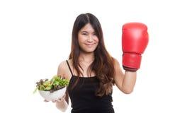 有拳击手套和沙拉的年轻亚裔妇女 库存图片