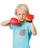 有拳击手套的严重的恼怒的男孩 免版税库存照片
