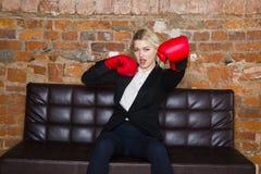有拳击手套的可爱的白肤金发的女实业家准备好在公寓前面的一次战斗 到达天空的企业概念金黄回归键所有权 免版税图库摄影