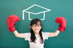 有拳击手套和毕业概念的小女孩 免版税库存图片