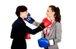 有拳击手套战斗的两个女商人 免版税库存图片