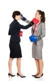 有拳击手套战斗的两个女商人 免版税库存照片