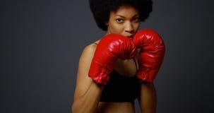 有拳击手套的坚强的黑人妇女运动员 免版税库存图片