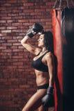 有拳击手套的年轻性感的女孩,沙袋 免版税库存照片